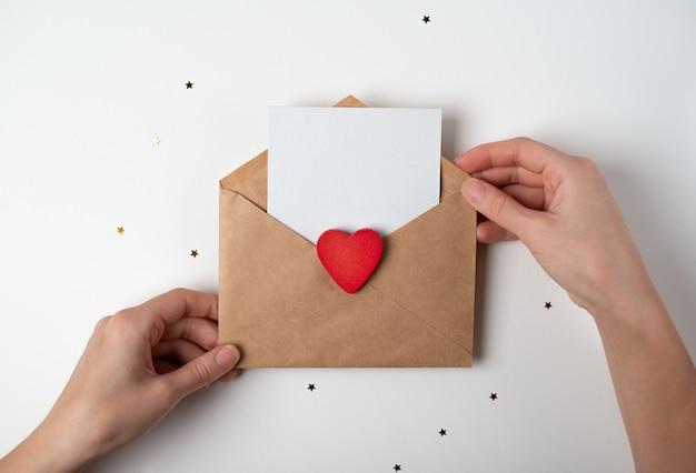 Wykonana ręcznie koperta z czerwonym sercem i czystą kartką papieru w dłoniach kobiety. koncepcja walentynki.