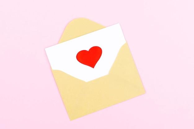 Wykonana ręcznie koperta z czerwonym sercem na białej karcie na pastelowym różowym tle. widok płaski, widok z góry. koncepcja walentynki. koncepcja dnia matki.