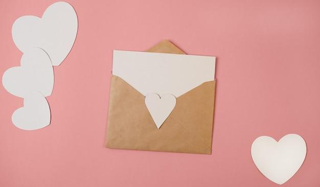 Wykonana ręcznie koperta z pustym papierem w środku i białymi papierowymi sercami na różowym tle. widok płaski, widok z góry. romantyczny list miłosny na walentynki.