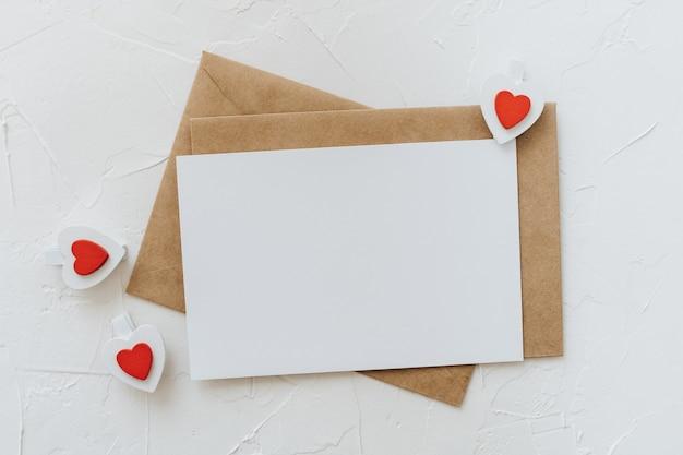 Wykonane ręcznie koperty, biała pusta kartka papieru i drewniane spinacze serduszka na białym tle. koncepcja walentynki.