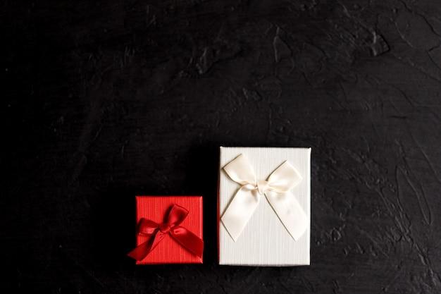 Wykonane ręcznie pudełko prezentowe na czarnym tle, ozdobione kokardką. na urodziny, prezenty rocznicowe, pocztówki upominkowe.