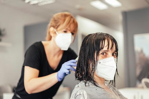 Wykonanie pracy ze wszystkimi środkami bezpieczeństwa. ponowne otwarcie ze środkami bezpieczeństwa fryzjerów w pandemii covid-19