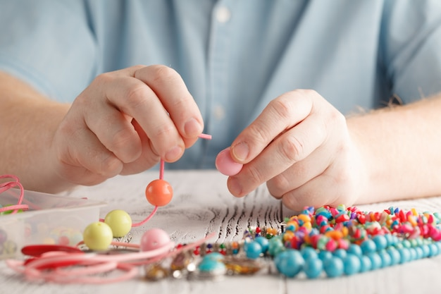 Wykonanie ręcznie robionej biżuterii, widok męskich dłoni z przodu
