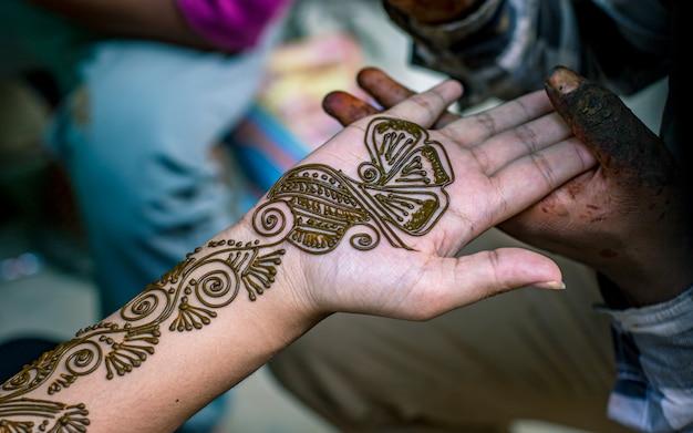 Wykonanie sztuki mehendi pod ręką podczas nepalskiego festiwalu rozpoczynającego się w katmandu w nepalu.