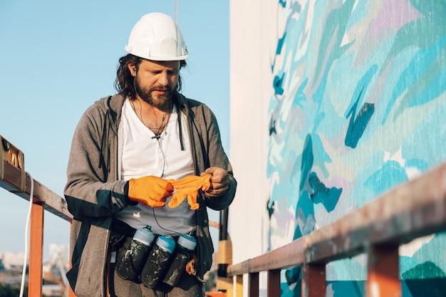 Wykonawca, artysta na dużej wysokości w kołysce budowlanej zakłada rękawiczki i przygotowuje się do wykonania malowania elewacji