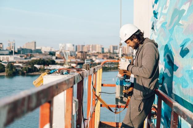 Wykonawca, artysta na dużej wysokości w kołysce budynku wybiera puszkę ze sprayem z pudełka, dekorując i remontując dom