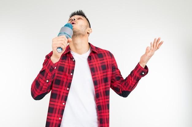 Wykonawca facet piosenkarz w koszuli z mikrofonem w jego ręce na białym tle