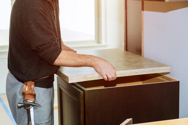 Wykonawca instaluje nowy blat kuchenny laminowany