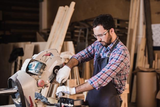 Wykonawca kadrowania za pomocą okrągłej piły do przycinania długości drewnianych kołków.