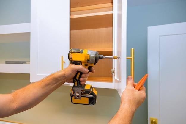 Wykonawca majsterkowania instaluje nowy zawias drzwi szafki kuchennej