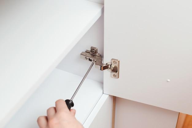 Wykonawca mechanik montujący nowe meble w nowoczesnym mieszkaniu. mężczyzna montuje białe drewniane meble za pomocą śrubokręta. motyw mebli mieszkaniowych. pracownik zbiera nową szafkę za pomocą narzędzia ręcznego.