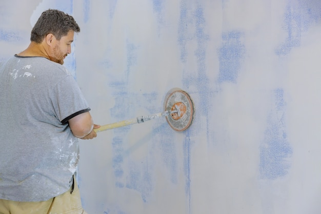 Wykonawca za pomocą pacy do piaskowania wyszlifuje płytę gipsowo-kartonową na ścianie
