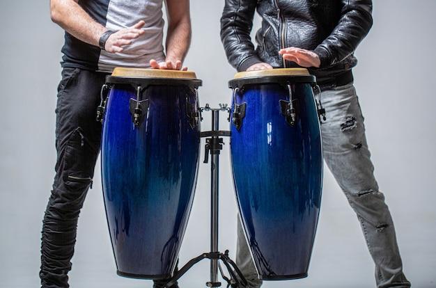 Wykonawcy grający na bębnach bongo. zbliżenie na rękę muzyk grający na perkusji bongosy. afro-kuba, rum, perkusista, palce, ręka, uderzenie. bęben. ręce muzyka grającego na bongach.