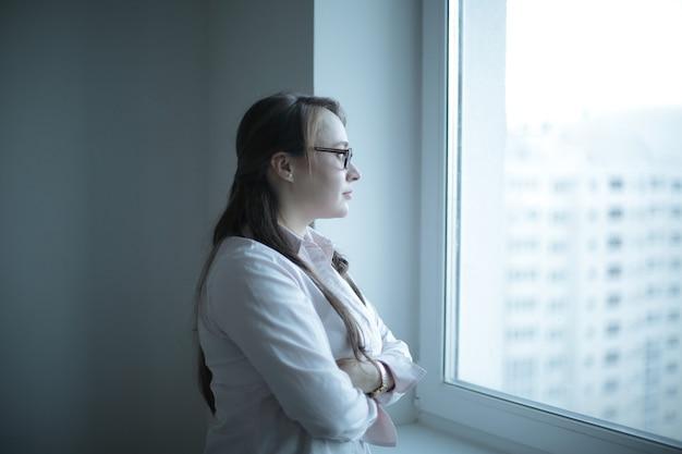 Wykonawcza kobieta biznesu patrząca przez okno biura