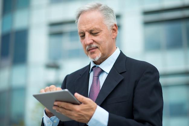 Wykonawczy za pomocą tabletu przed swoim biurem