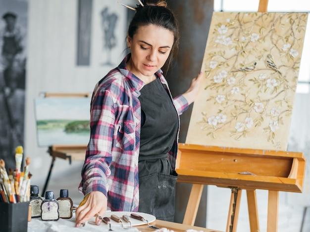Wykończenie grafiki. płótno z kwiatami i ptakami. miejsce pracy pracowni artystycznej. kobieta artysta wybierając narzędzie do modelowania.