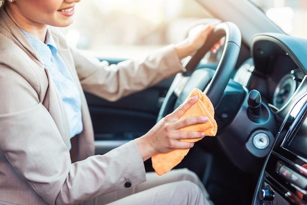 Wykończenie wnętrza samochodu. szczęśliwa kobieta wyciera i czyści wnętrze swojego samochodu.