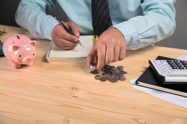 Wykonuje obliczenia i pisze w zeszycie, obok skarbonki i monet