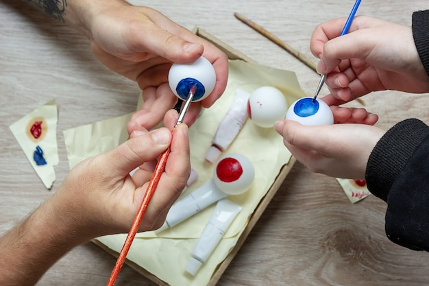Wykonujemy dekorację na halloween, malujemy gałkę oczną na piłce tenisowej farbami. diy rzemiosło z dzieckiemr
