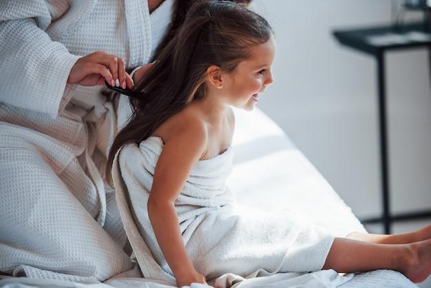 Wykonywanie fryzury grzebieniem. młoda matka z córką mają dzień urody w pomieszczeniu w białym pokoju.