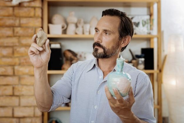 Wykonywanie zamówienia. niebieskooki brodaty ceramista ciężko pracuje w swoim warsztacie, wykonując zamówienia dla klientów