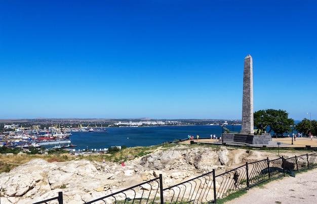 Wykopaliska archeologiczne w ruinach starożytnego greckiego miasta panticapaeum z widokiem na obelisk chwały nieśmiertelnych bohaterów na górze mitrydates i na morzu czarnym