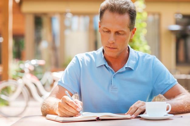 Wykorzystując chwilę do robienia notatek. pewny siebie dojrzały mężczyzna piszący coś w swoim notesie siedząc przy stole na zewnątrz z domem w tle