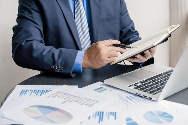 Wykres analizy biznesmena z laptopem w domowym biurze do wyznaczania ambitnych celów biznesowych