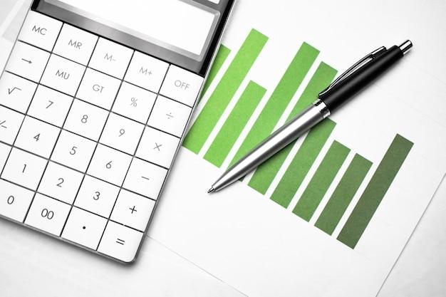 Wykres biznesowy pokazujący sukces finansowy na giełdzie za pomocą pióra i kalkulatora