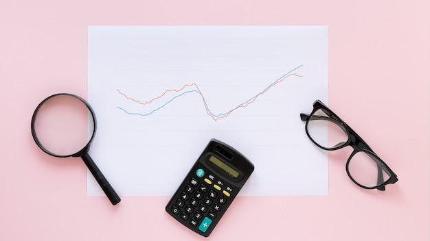 Wykres ekonomiczny na kartce papieru z lupą