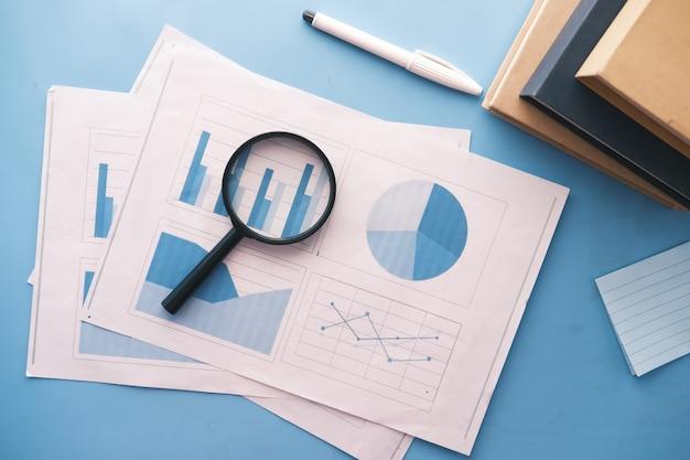 Wykres finansowy, szkło powiększające i notatnik na stole