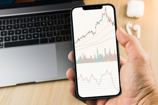 Wykres giełdy finansowej na ekranie smartfona na drewnianym tle z komputerem obok niego. giełda papierów wartościowych.