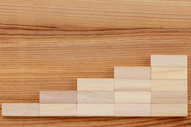 Wykres lub drewniane kroki na drewnianym tle. koncepcja celów strategii biznesowej sukcesu.