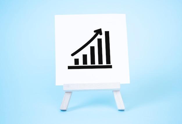 Wykres sztalugi i strzałki w górę. koncepcja sukcesu, wzrostu i poprawy wydajności. statystyka i analityka biznesowa. dochód z dochodów