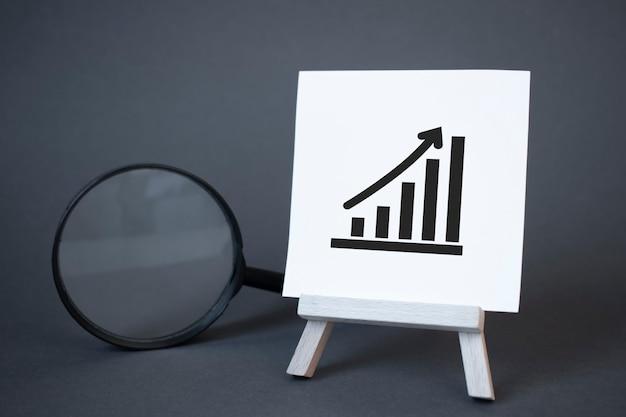 Wykres sztalugi, lupy i strzałki w górę. koncepcja sukcesu, wzrostu i poprawy wydajności. statystyka i analityka biznesowa. dochód z dochodów