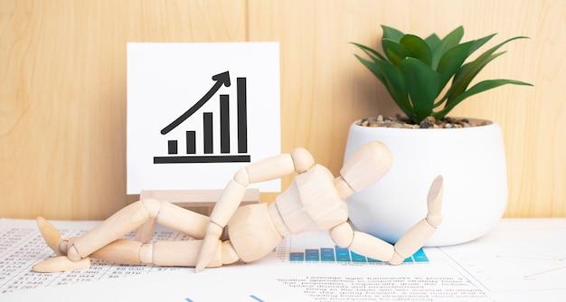 Wykres ze strzałką w górę na sztalugach z narzędziami biurowymi i papierem. widok z góry.
