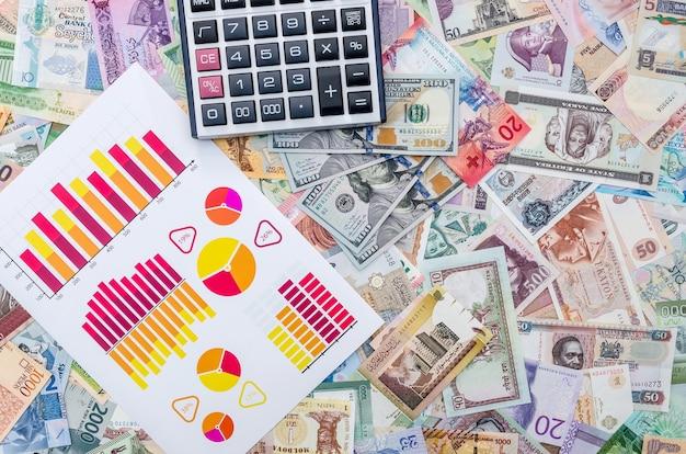 Wykresy biznesowe i kalkulator na kolekcji banknotów