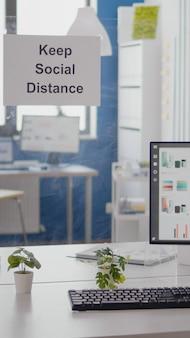 Wykresy działalności finansowej w pustym biurze bez nikogo w nim, zachowaj znaki odległości społecznej na ścianie