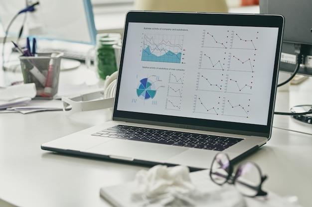 Wykresy finansowe i diagram na wyświetlaczu laptopa w miejscu pracy współczesnego brokera lub bankiera, którego w danej chwili nie ma