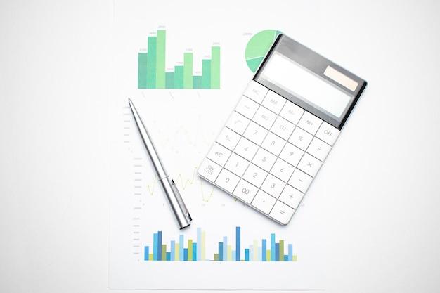 Wykresy finansowe i kalkulator na biurku księgowego. obliczanie zysków, podatków i płacenie wynagrodzeń pracownikom.