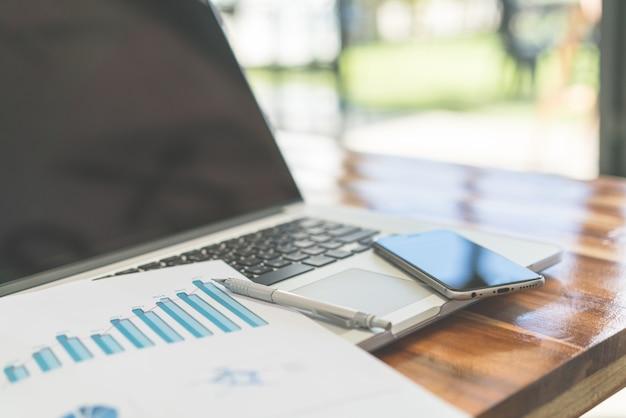 Wykresy finansowe na stole z laptopem. (filtrowane zdjęcie pr
