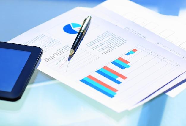 Wykresy finansowe na stole z tabletem i piórem