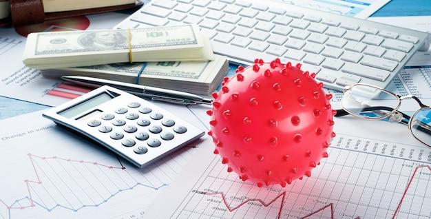 Wykresy i histogramy, koronawirus, pieniądze, kalkulator na stole. spadek światowej gospodarki i dochodów.