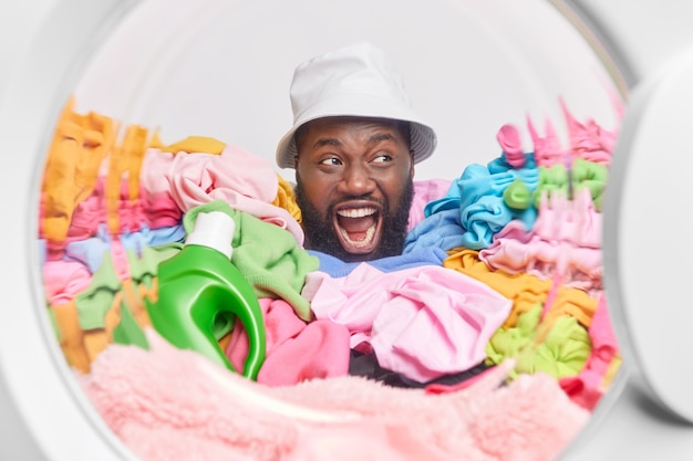 Wykrzykuje głośno mężczyzna trzyma szeroko otwarte usta odwraca wzrok pozuje wokół wielokolorowego prania z płynnym proszkiem zajęty praniem w domu