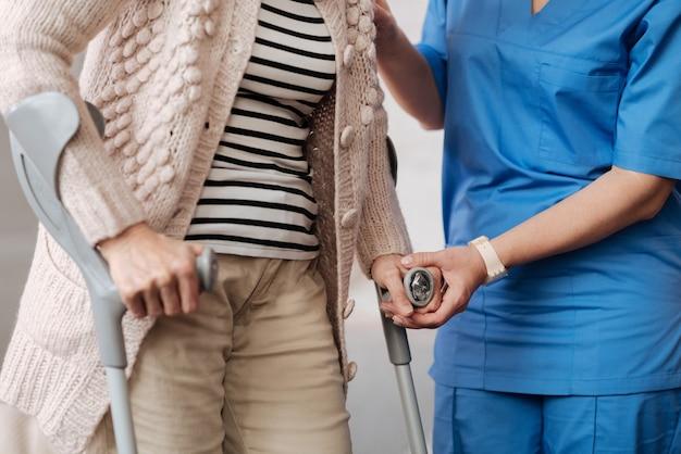 Wykwalifikowana kopia zapasowa. zaangażowany uprzejmy wyszkolony lekarz wykonujący swoją pracę i pomagający starszej kobiecie na spacerze o kulach