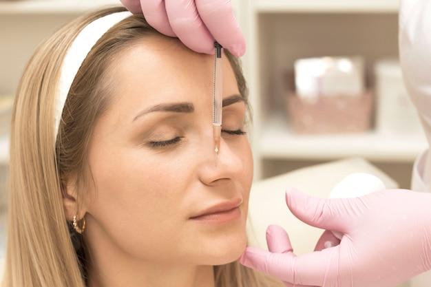 Wykwalifikowana kosmetyczka trzymająca klientkę w nosie i wykonująca zabieg iniekcyjny za pomocą strzykawki z kwasem hialuronowym