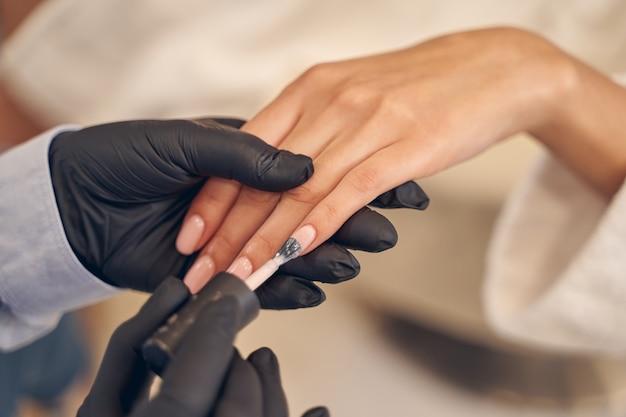 Wykwalifikowana mistrzyni salonu posługuje się pędzelkiem i dokładnie poleruje paznokcie klientów pastelowym kolorem