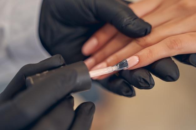 Wykwalifikowana mistrzyni urody poleruje paznokcie klientek o beżowym kolorze przy użyciu pędzla