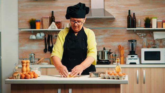 Wykwalifikowana stara kobieta naprawia ciasto do pieczenia w nowoczesnej domowej kuchni. emerytowany starszy kucharz z bonete i jednolitym posypaniem, przesiewając mąkę pszenną z ręcznym pieczeniem domowej pizzy i chleba.