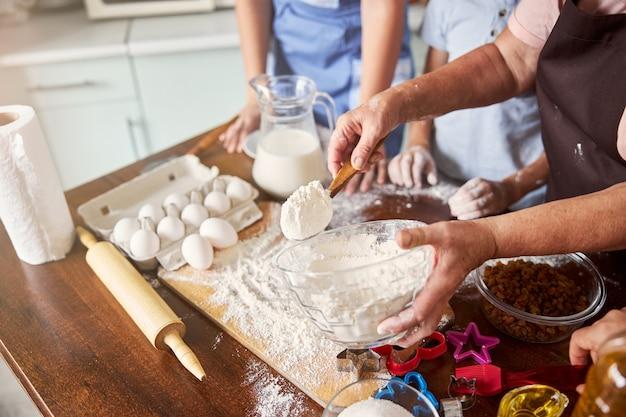 Wykwalifikowana starsza pani biorąca trochę mąki do robienia ciasta